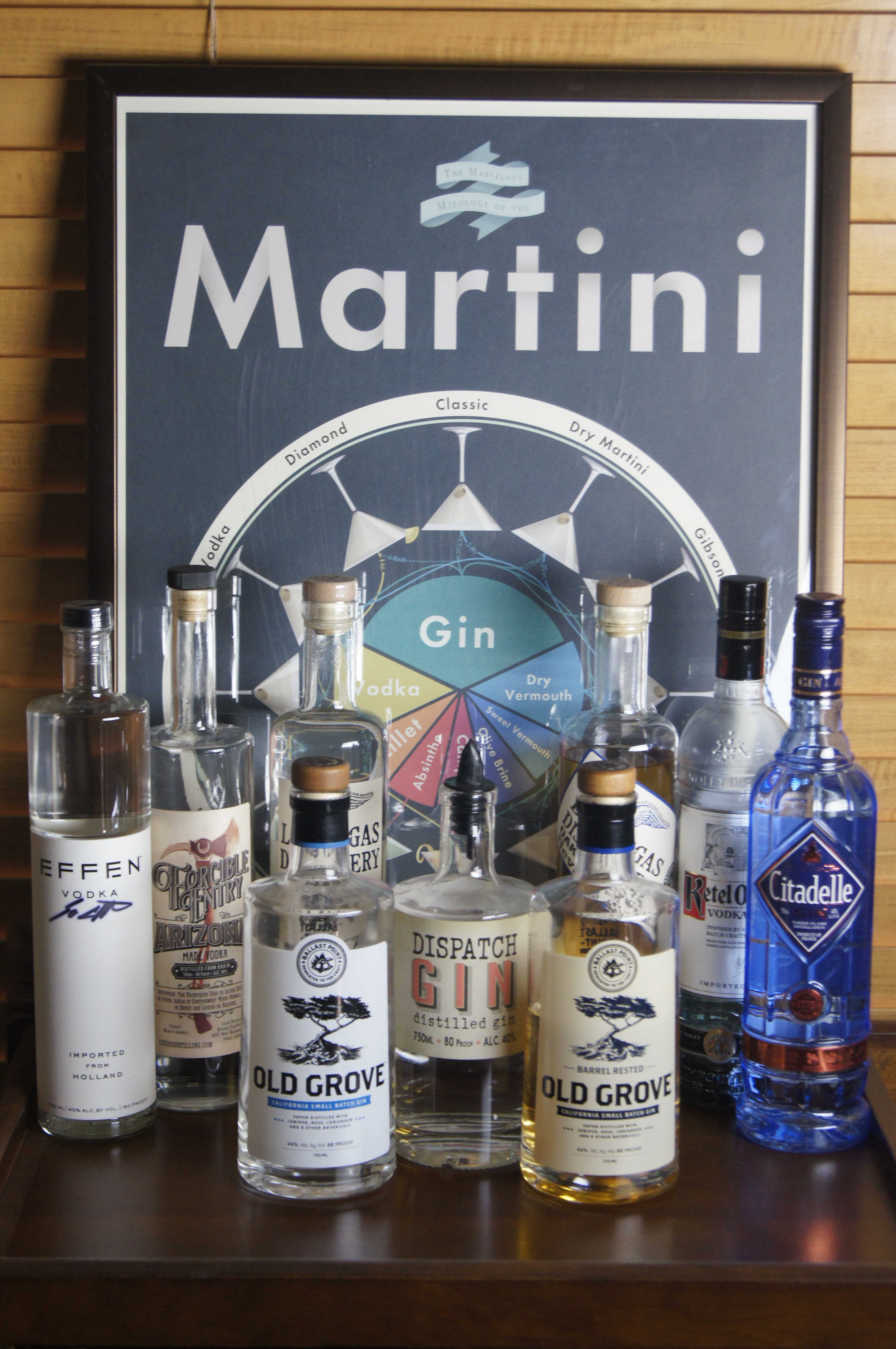 A martini poster behind a selection of 12 various vodka and gin bottles.