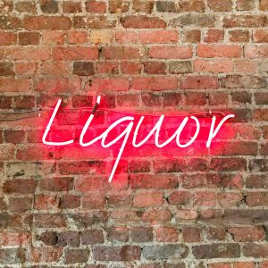 image of a pink neon sign that spells 'Liquor' placed over a red brick wall